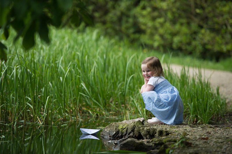 Girl in blue dress plays with paper boat in Johnstown castle wexford during family portrait session