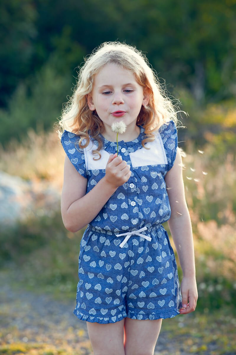 girl blowing dandelion durin family photography session in forth mountain Wexford