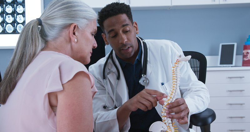 senior woman at pain treatment center listening to male doctor pointing at spine figure