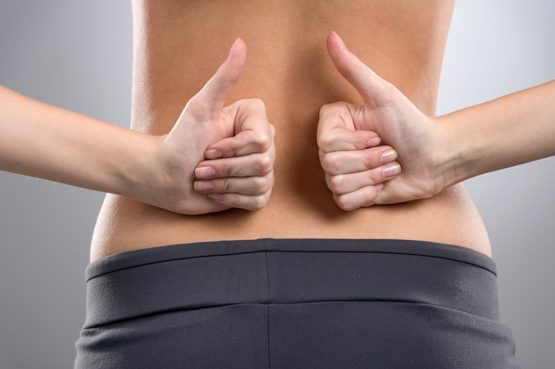 woman back pain with thumbs up after treatment at our pain treatment centers