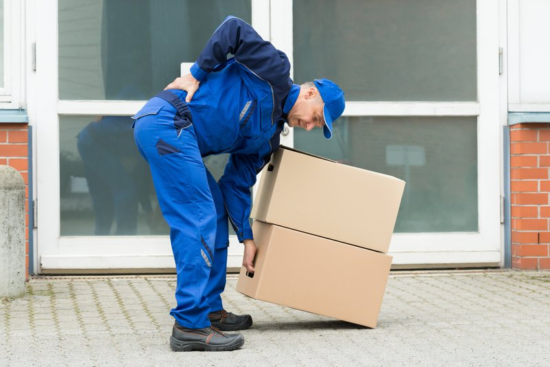 man bending over with back pain picking up boxes