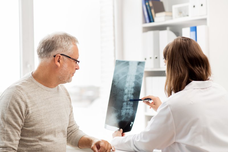 female doctor pointing to spine xray to male patient at pain treatment center