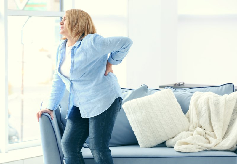 woman holding back in pain contemplating visiting a pain treatment center