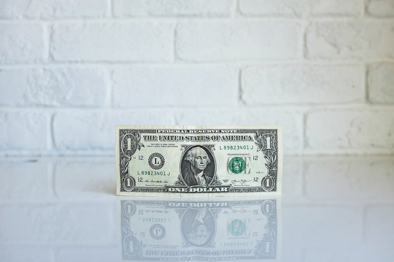 One dollar bill by the wall