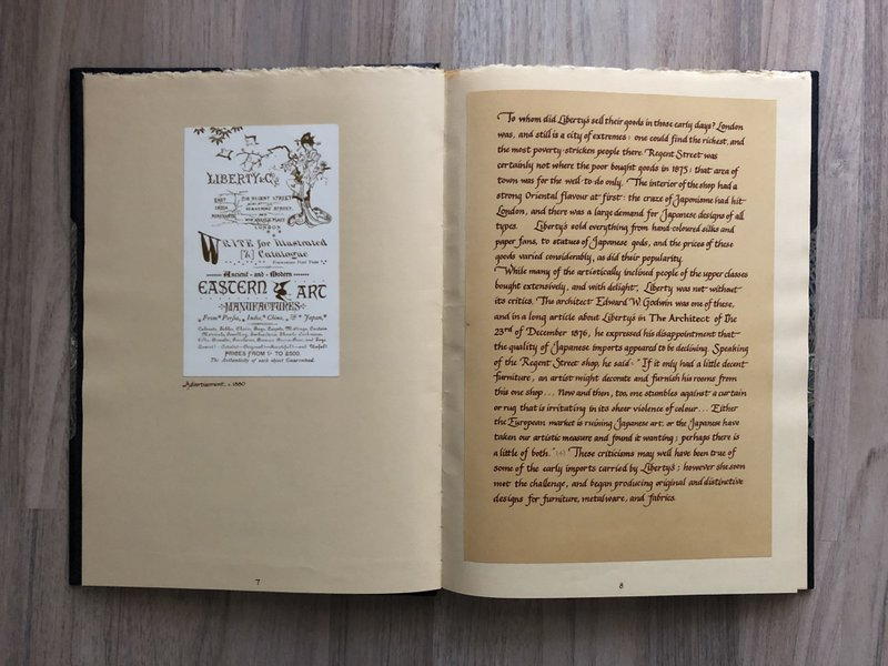 Open book with a small poster on the left, and a page of calligraphic text on the right.