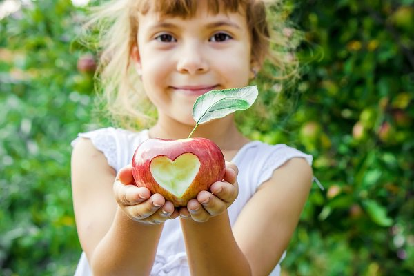 Child with an apple. Selective focus. Garden Food
