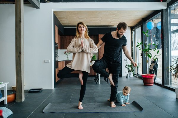 Family doing yoga. Mother standing in a position, keeping balance, while father smiling down at their child creeping on all fours at his feet.