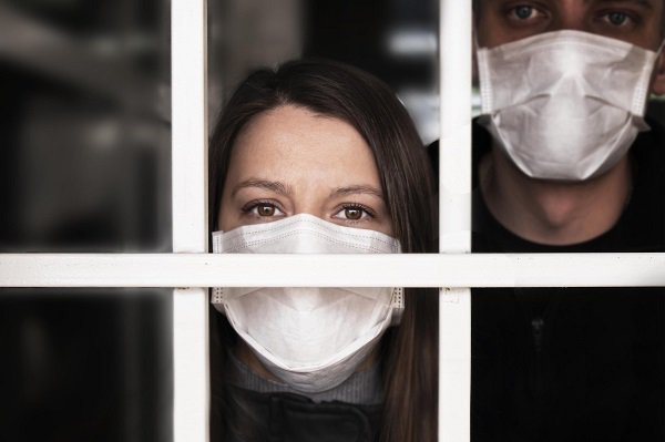 A man and woman behind a glass window showing hints of anxiety in their eyes