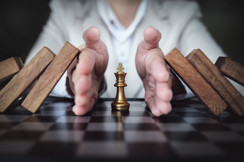 Preventing the risk of playing chess on a business board, business insurance concept.