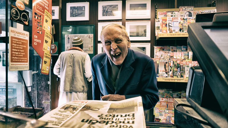 Old man in a store laughing seems like a satisfied and loyal customer.
