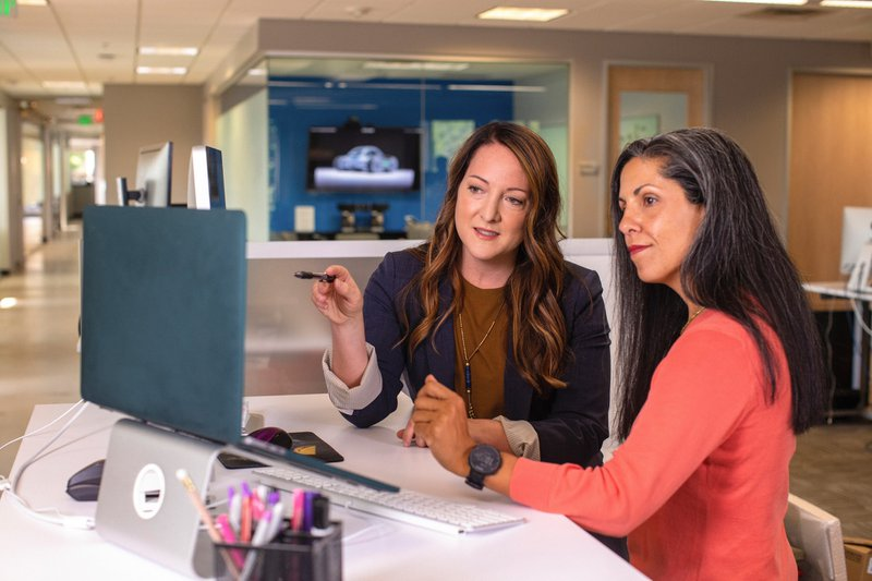 Two business women talking about sales in office at desk with laptop