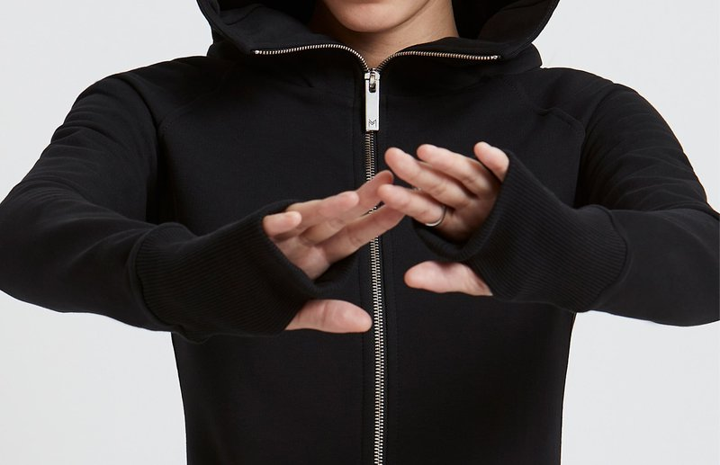 person with black sweater and zipper hands streched out-MarcellaModa NYC