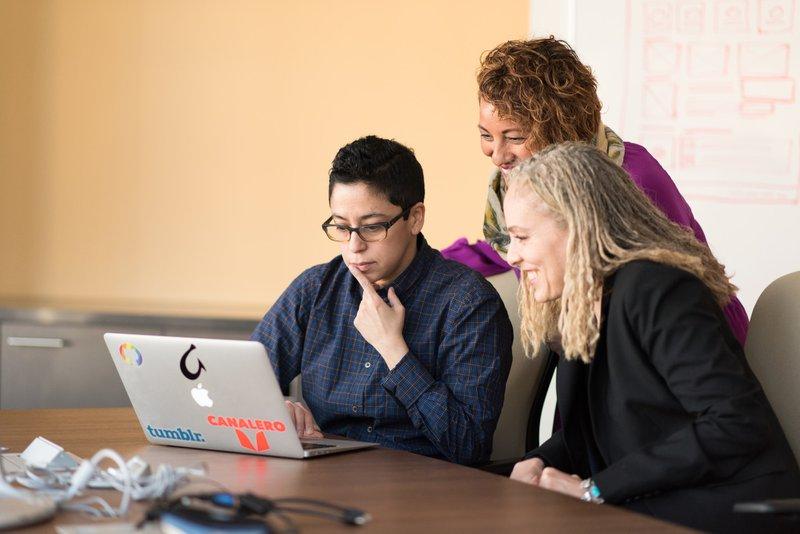 three women beside table looking at MacBook