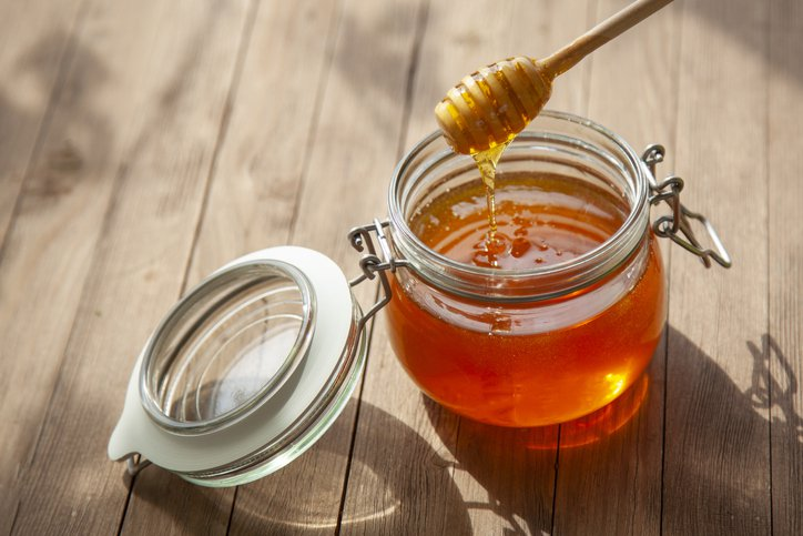 Pot Of Honey And Wooden Stick Are On A Table outdoors.