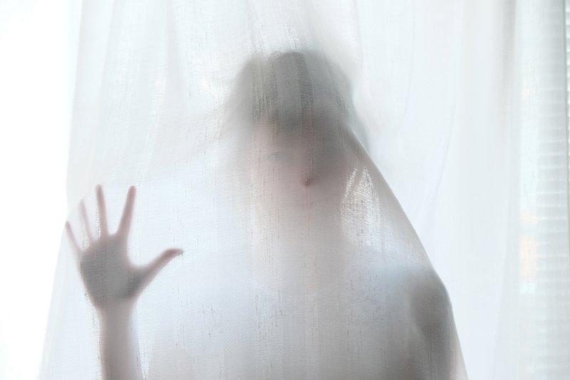 Girl touching a shower curtain