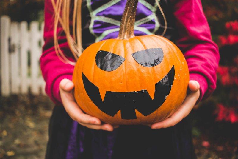 Child holding jack-o-lantern