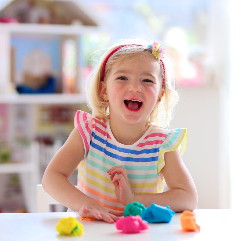 Little preschooler girl playing with plasticine. Happy child, adorable creative toddler girl playing with dough, colorful modeling compound, sitting at white table in bright sunny room at home or kindergarten