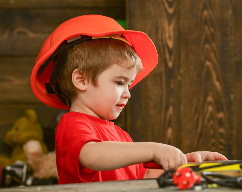 Kid play at table with tools. Handcrafting concept. Child in helmet cute playing as builder or repairer, repairing or handcrafting. Toddler on busy face plays at home in workshop.