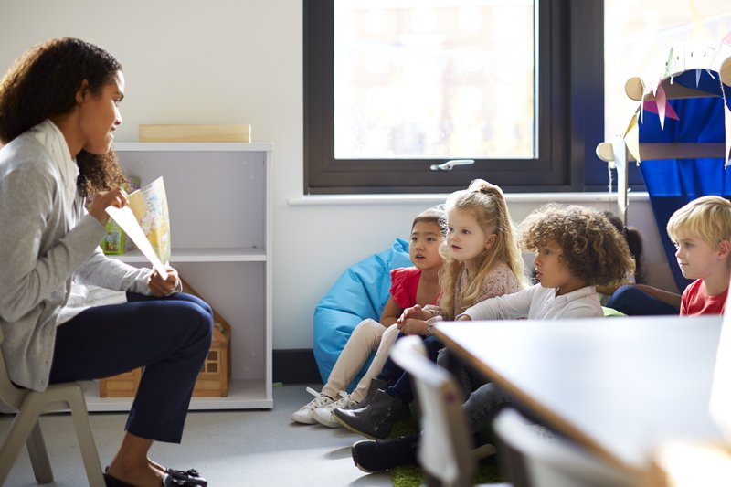 Side view of a female kindergarten teacher sitting on a chair showing a book to children in a classroom