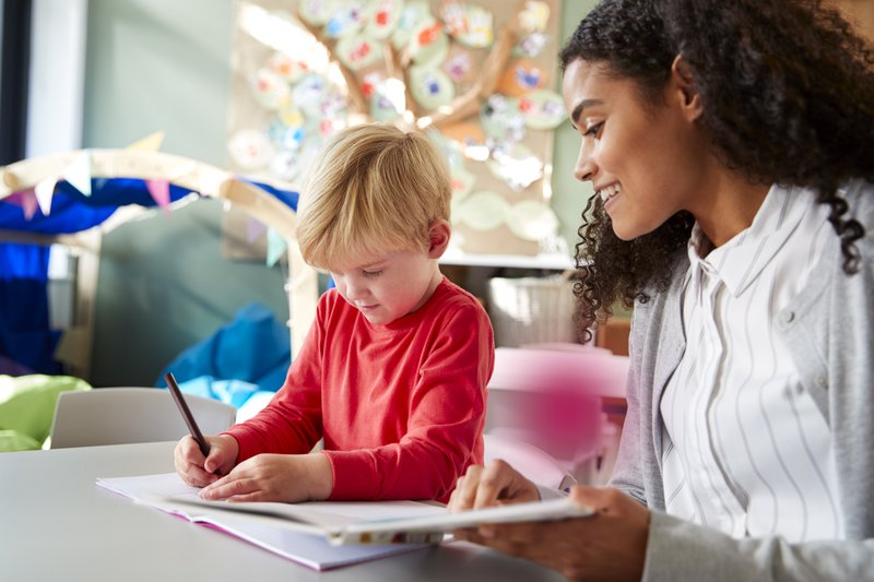 Female infant school teacher working one on one with a young white schoolboy, sitting at a table in a classroom writing, close up