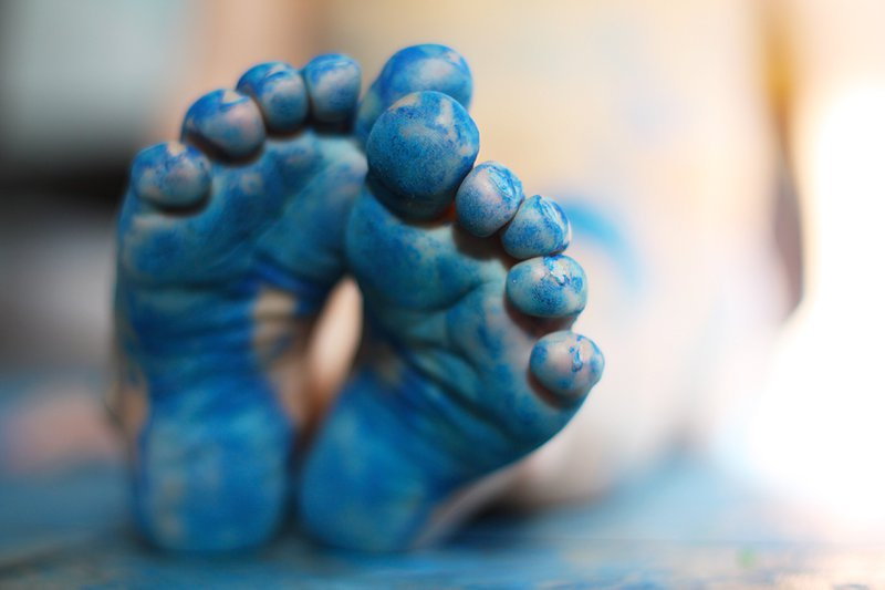 a close up on the bottom of the feet of a small child, that have been painted blue.  Very shallow depth of field with focus on toes of front foot.