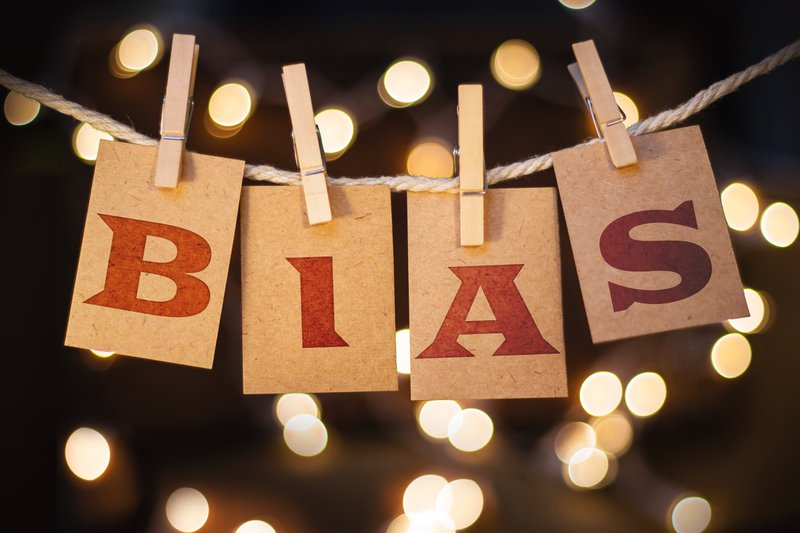The word BIAS printed on clothespin clipped cards in front of defocused glowing lights.
