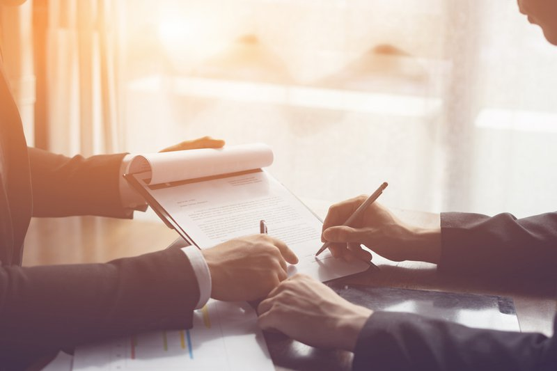 Businessperson Signing Contract about insurance, Two men writing with pen sign of modest agreements form In modern office, morning light, vintage color, success of business partners concept