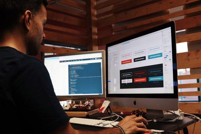 Programmer coding inside a no code web design tool