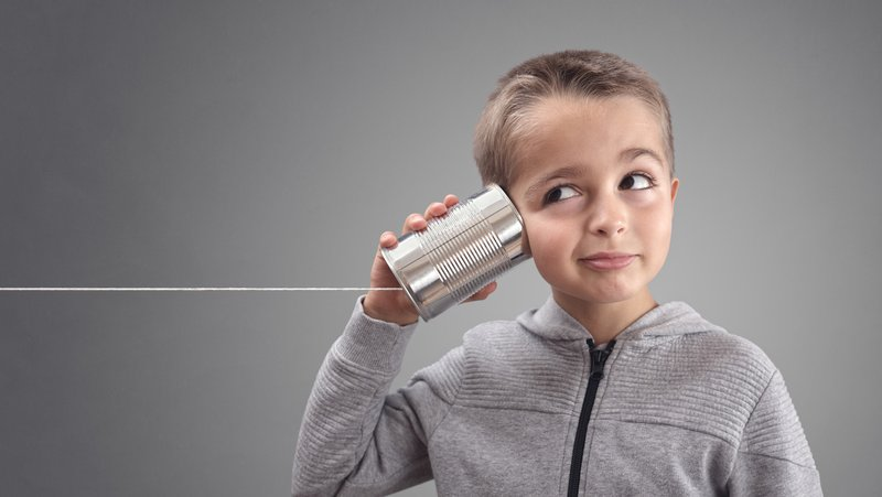 boy listening through can and string phone