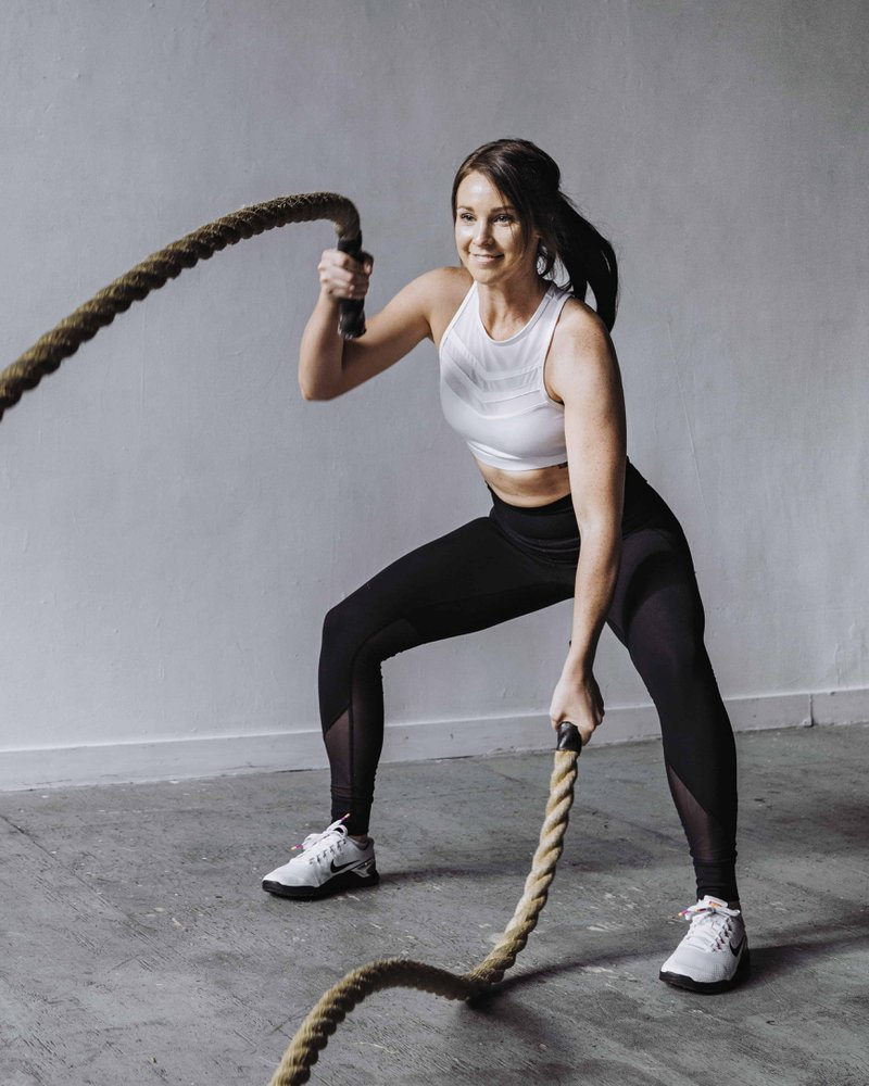 Athletic woman exercising with ropes