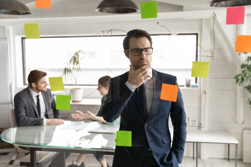 Pensive Caucasian young businessman busy pondering develop business strategy ideas on sticky notes on glass wall. Thoughtful male employee do creative thinking plan or brainstorm in office boardroom.