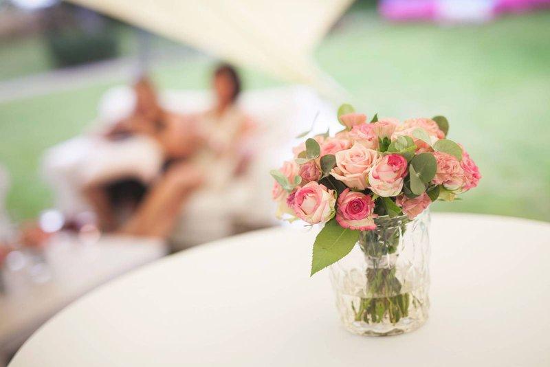 Roze bloemen in vaas op receptietafel onder tent trouwfeest - House of Weddings