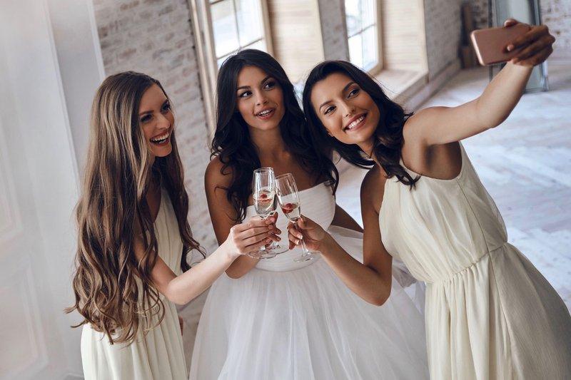 Bruid neemt selfie met bruidsmeisjes met smartphone - House of Weddings