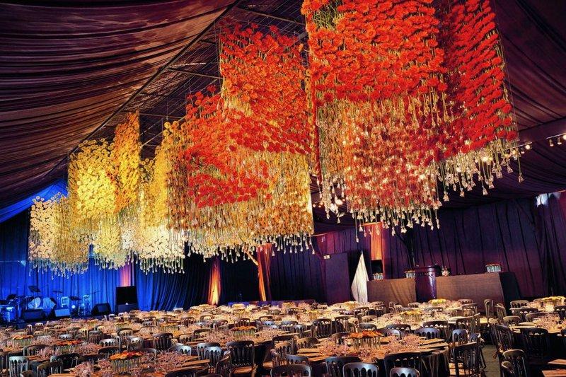 Kleurrijke hangende bloemtapijten boven eettafels door Daniële & Nele Ost - Hangende bloemen - Florale Creaties - Bloemenplafond - Rode bloemen - - Bloemen Backdrop - House of Weddings
