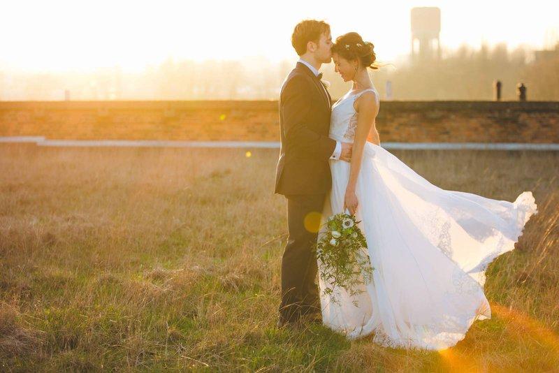 Bruidspaar in grasveld bij golden hour - Lux Photography - House of Weddings