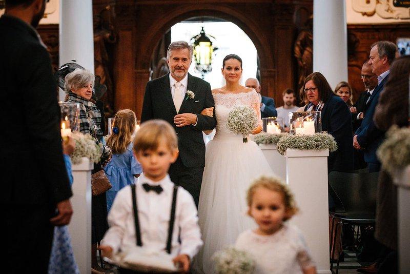 Intrede bruid met vader van de bruid en bruidskindjes in kerk - House of Weddings