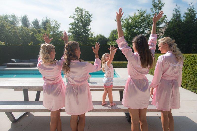 Bruidsmeisjes in roze komono's in de tuin met zwembad - House of Weddings