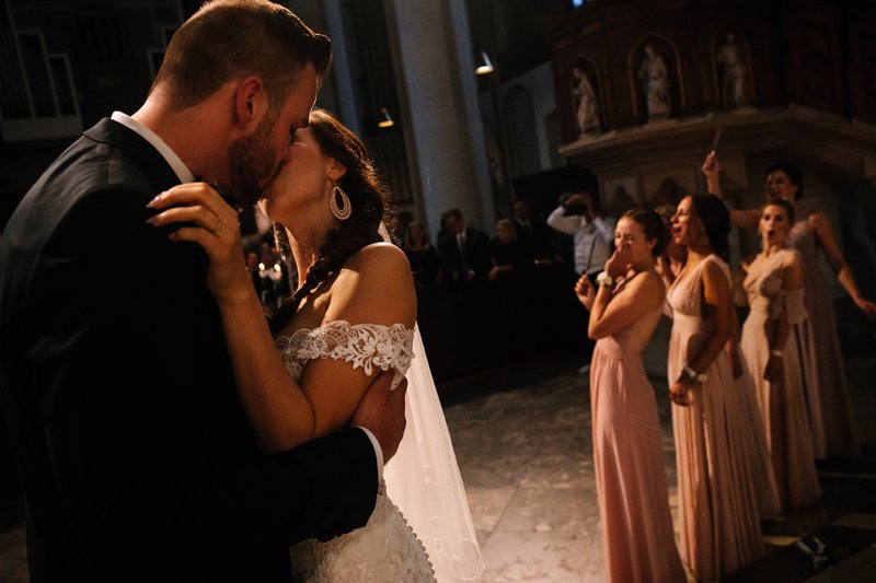 Bruidspaar deelt kus op de dansvloer terwijl bruidsmeisjes in zachtroze lange jurken toejuichen - House of Weddings