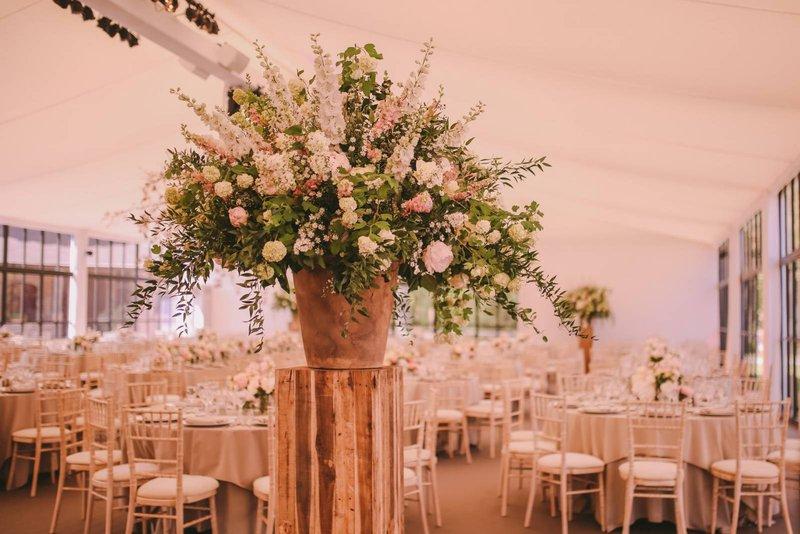 Groot, wild boeket in vaas op pilaar - Annick Van Wesemael - House of Weddings