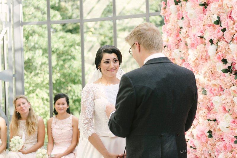 Koppel - Trouwgeloften - Roze bloemenwand - Gelukkig - Bruidsmeisjes achtergrond - House of Weddings