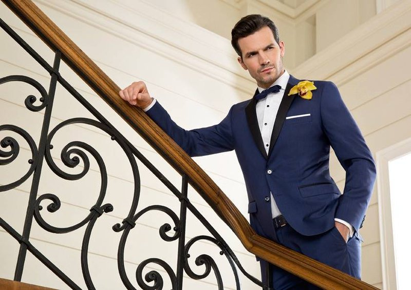Bruidegom met blauw maatpak, vlinderdas en pochet - Herenmode De Waele - House of Weddings