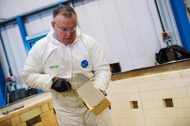 Refractory mason laying thermally efficient fire brick in an incinerator