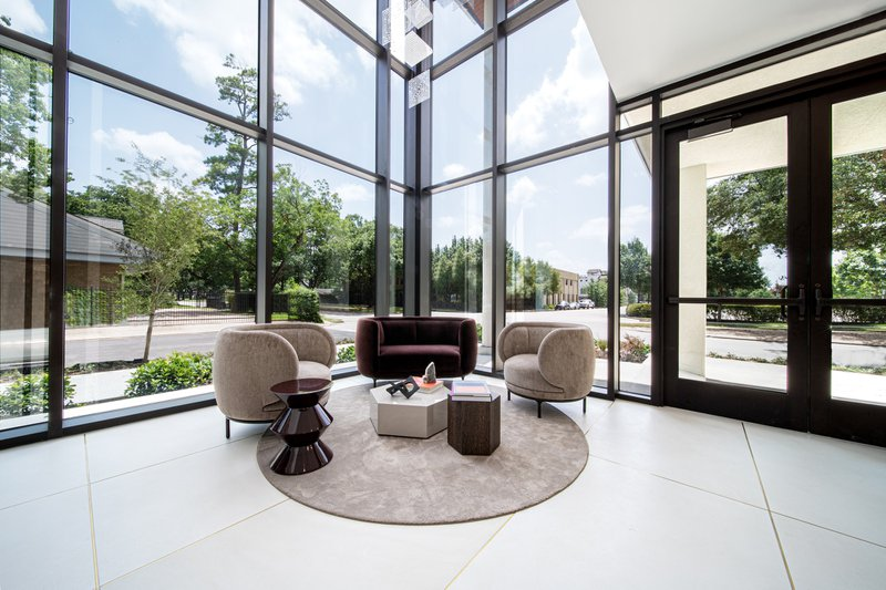 The seating area of an entrance lobby of a modern condominium building with large windows, natural light, and trees in the background.