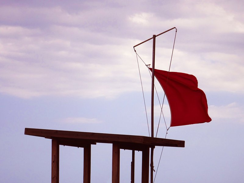 Red flag on a beach at a lifeguard tower with a cloudy sky.