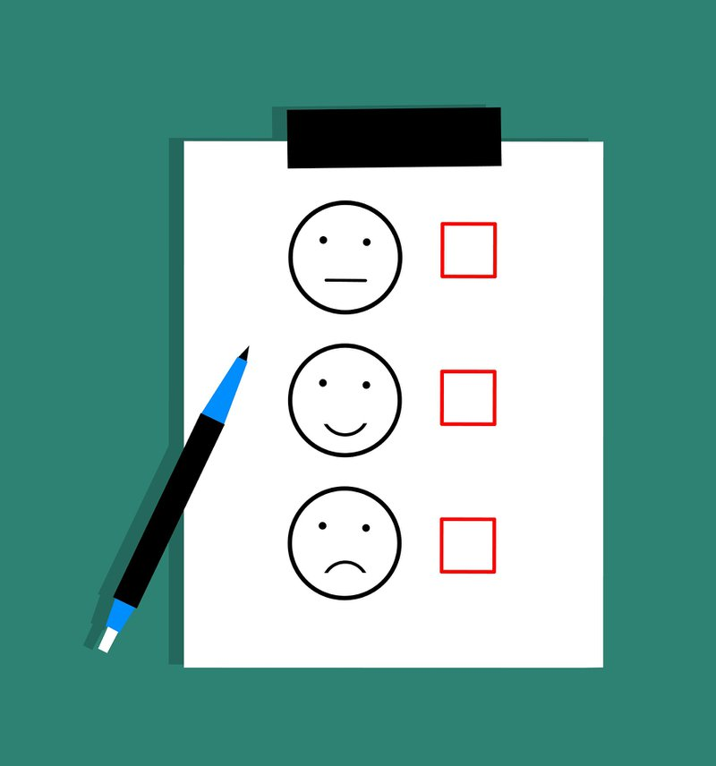 paper with multiple choice options of a neutral face, happy face, and sad face with pen laying beside it