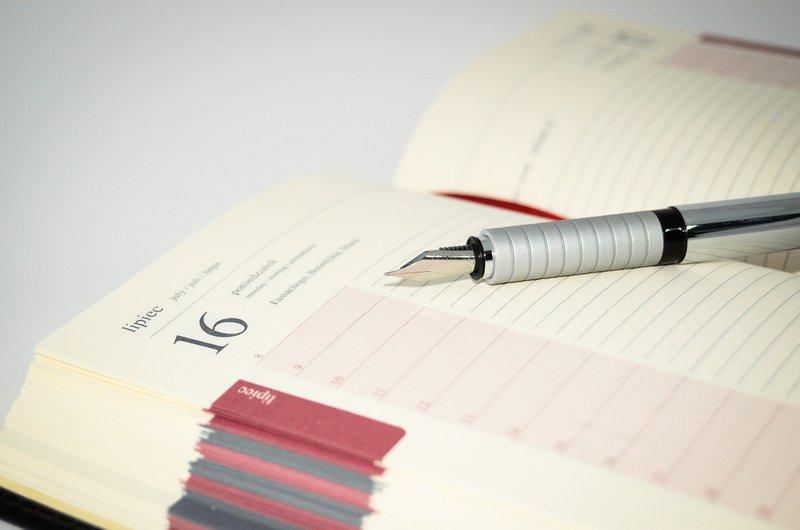 Open agenda with a pen lying on it