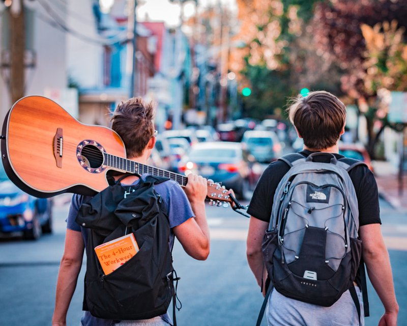 "Digital Nomads walking through city with guitar and 4-hour work week book. // Photographer: Austin Distel | Source: Unsplash ""www.distel.co"". ❤️"