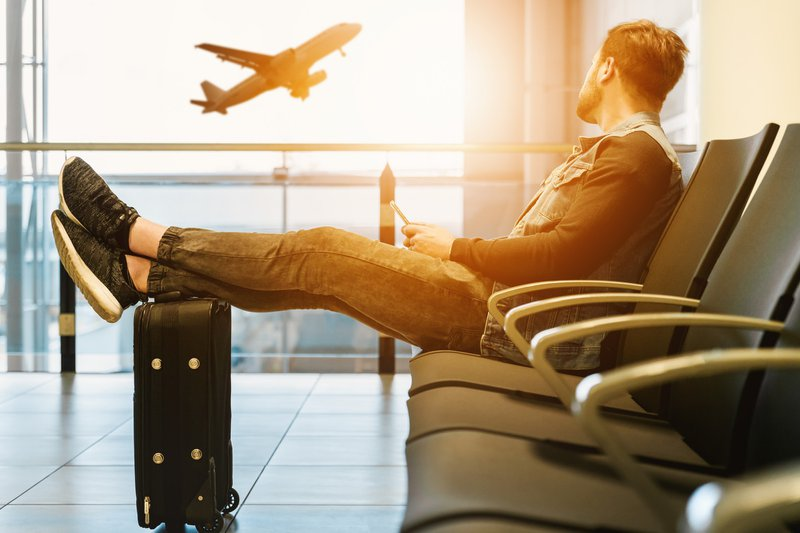 man sitting at gate watching a plane take off out the window with the rising sun // Photographer: JESHOOTS.COM | Source: Unsplash