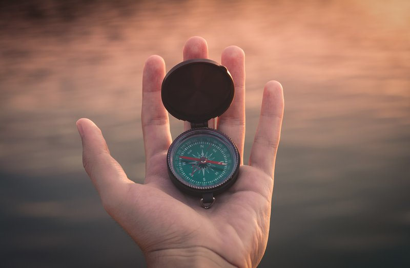 compass in the palm of a hand above water // Photographer: Aron Visuals | Source: Unsplash