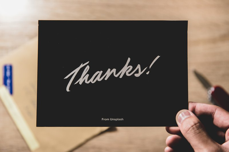 person holding thank you card